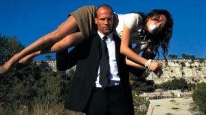 jason statham as transporter with girl hostage over his shoulders from The Transporter